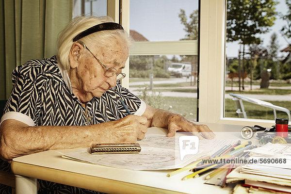 Zeichnende alte Frau