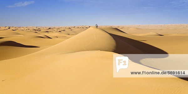 Photographer standing on a sand dune in the Libyan Desert  Libya  Africa