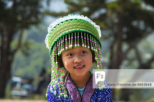 Smiling little girl in a traditional dress  costume  New Year festival  Hmong hill tribe  ethnic minority  Chiang Mai province  northern Thailand  Thailand  Asia