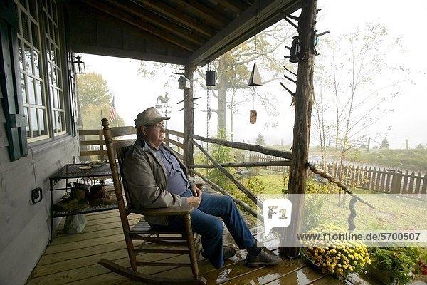 Mann sitzt im schaukelstuhl auf der veranda for Schaukelstuhl auf englisch