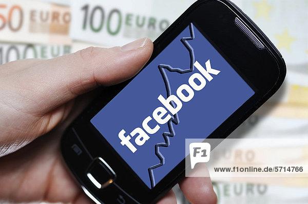 Hand mit Smartphone und Facebook-Logo vor Euroscheinen  Symbolbild Börsengang von Facebook