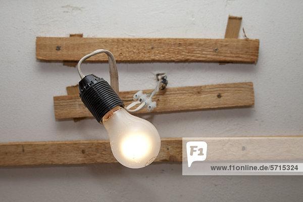 Glühlampe mit Lüsterklemmen und Holzleisten unter der Decke eines Wohnraums Glühlampe mit Lüsterklemmen und Holzleisten unter der Decke eines Wohnraums