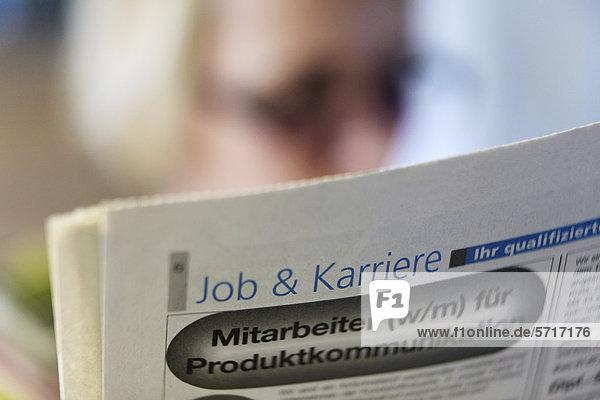 Jobsuche  Frau liest Stellenangebote in der Zeitung