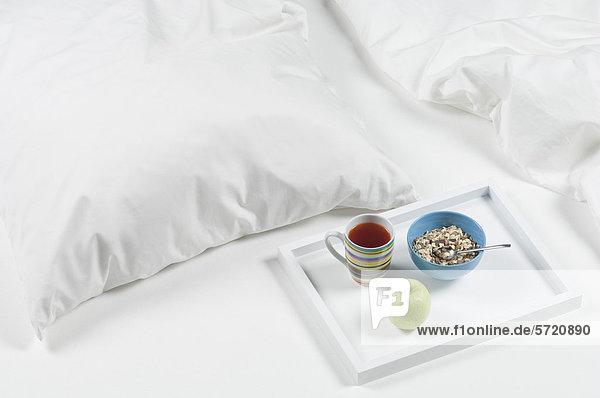 Tablett mit Tee  Apfel und Müsli auf dem Bett zum Frühstück