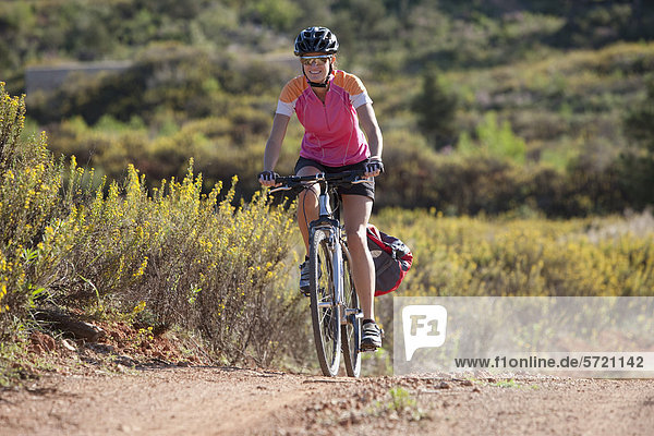 Spanien  Ibiza  Mid adult woman riding bicycle