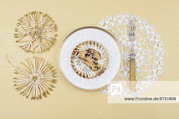 Weihnachtskuchen im Teller mit Strohstern-Dekoration auf cremefarbenem Hintergrund