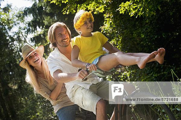 Österreich  Salzburger Land  Familie sitzend auf altem Fahrrad