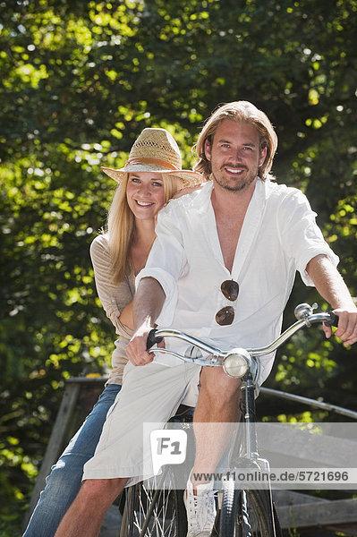 Österreich  Salzburg  Paar sitzend auf altem Fahrrad