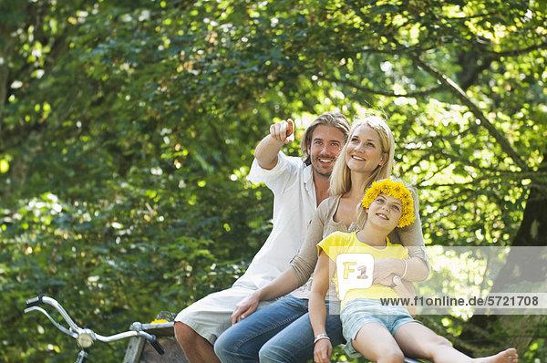 Österreich  Salzburger Land  Familie auf dem Zaun sitzend