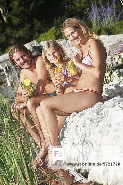 Österreich  Salzburger Land  Familie sitzend am Pool