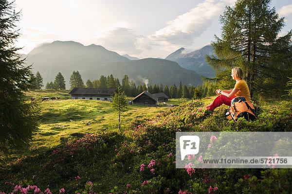 Österreich  Salzburger Land  Junge Frau sitzt auf einer Alm und beobachtet Landschaft