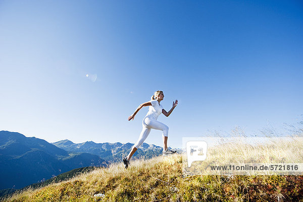 Austria  Salzburg County  Young woman running in alpine meadow