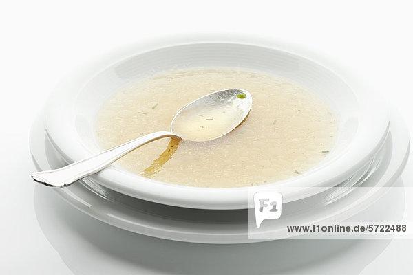Rindsuppe im Teller mit Löffel auf weißem Grund