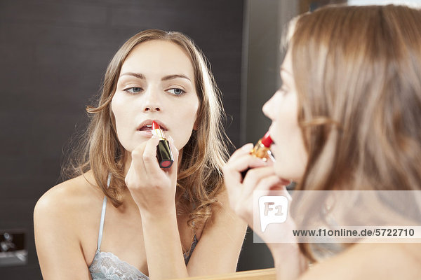 Young woman applying red lipstick in bathroom