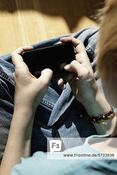 Junge  der mit einem elektronischen Gerät spielt.