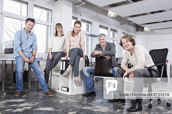 Männer und Frauen im Büro  lächelnd  Porträt