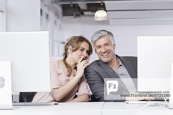 Frau flüstert im Büro ins Ohr des Mannes