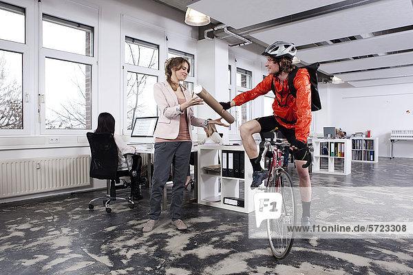 Kuriermann übergibt Paket an Frau im Amt