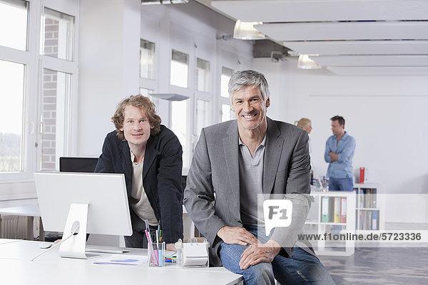 Männer sitzen am Computertisch im Büro