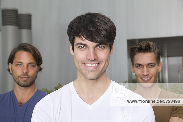 Deutschland  Nordrhein-Westfalen  Düsseldorf  Drei Auszubildende vor dem Gebäude  lächelnd  Portrait