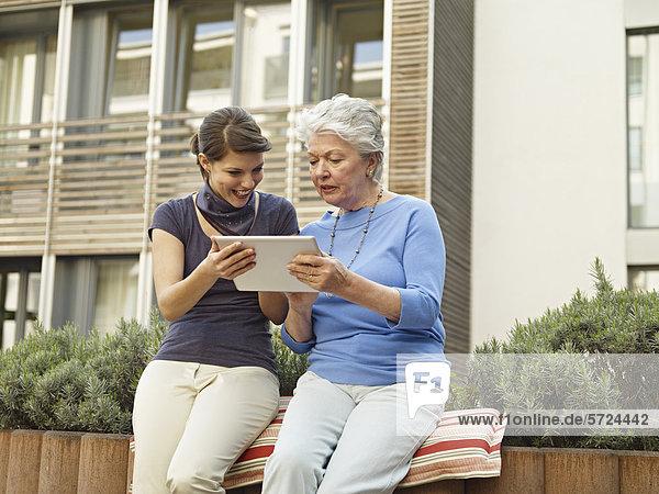 Frauen suchen digitale Tablette außerhalb des Pflegeheims