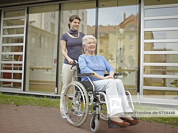 Frauen  die ältere Frauen im Rollstuhl außerhalb des Pflegeheims schieben.