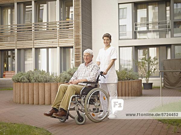 Hausmeister schiebt älteren Mann im Rollstuhl außerhalb des Pflegeheims