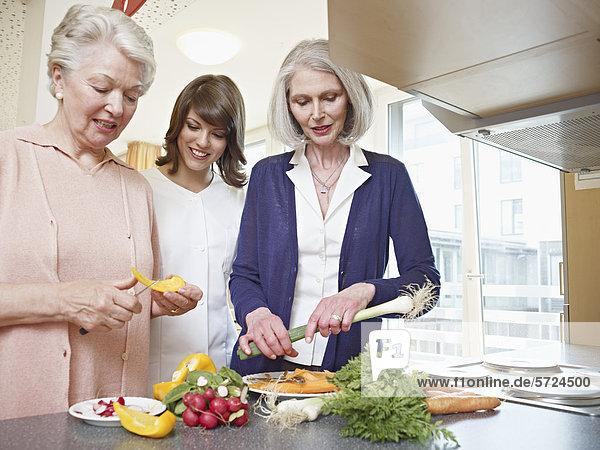 Frauen bei der Zubereitung von Speisen im Pflegeheim
