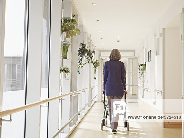 Seniorin mit Gehhilfe am Flur im Pflegeheim