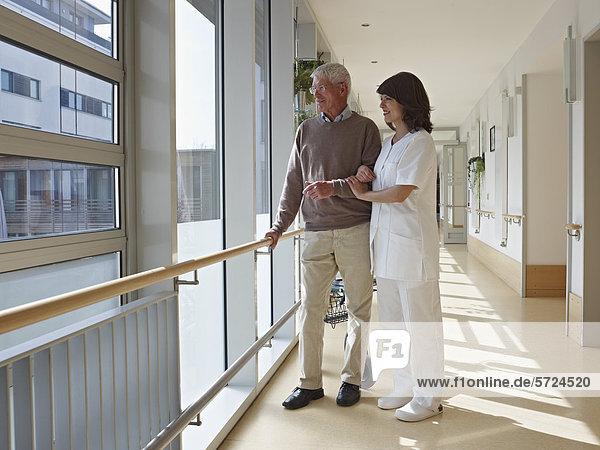 Älterer Mann und Hausmeister im Flur stehend und durchs Fenster schauend