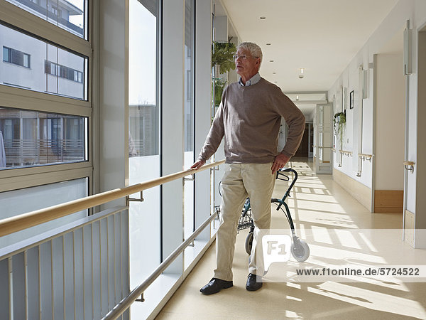Senior im Flur des Pflegeheims stehend  Gehhilfe im Hintergrund