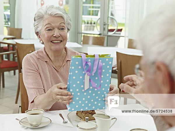 Seniorenfrau schenkt dem Mann
