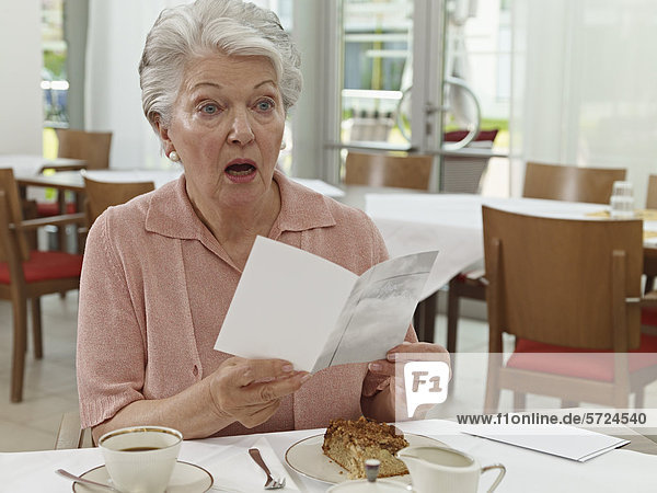 Seniorin mit Karte im Pflegeheim