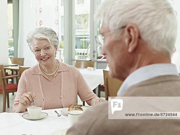 Deutschland  Köln  Seniorenpaar am Tisch sitzend  lächelnd