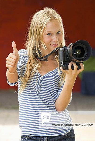 Österreich  Teenagermädchen mit Kamera  lächelnd