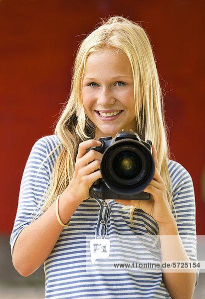 Österreich  Teenagerin mit Kamera  lächelnd  Portrait