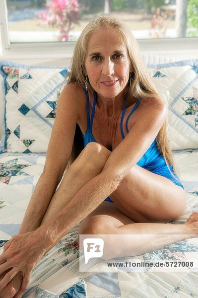sitzend  Portrait  Frau  lächeln  Bett  lang  langes  langer  lange  Blick in die Kamera  Haar  alt  Jahr