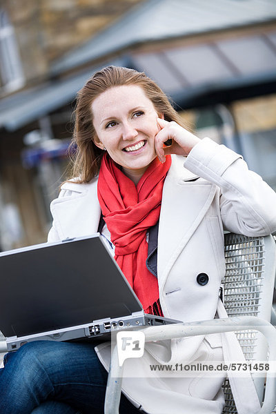 Young woman with laptop at rail station