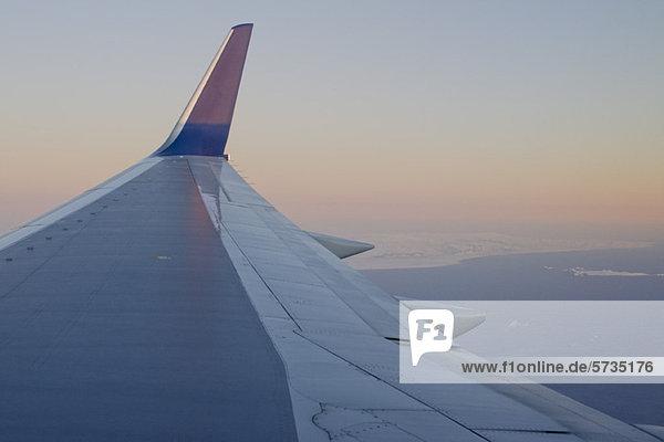Ansicht des Flugzeugflügels über der Küste Islands
