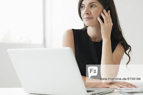 Mittlere erwachsene Frau am Schreibtisch sitzend mit Laptop  am Handy sprechend