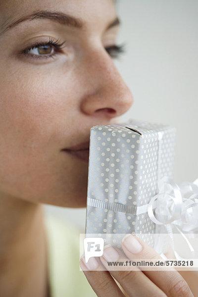 Frau küsst verpacktes Geschenk