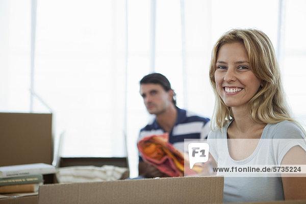 Junge Frau beim Auspacken im neuen Haus