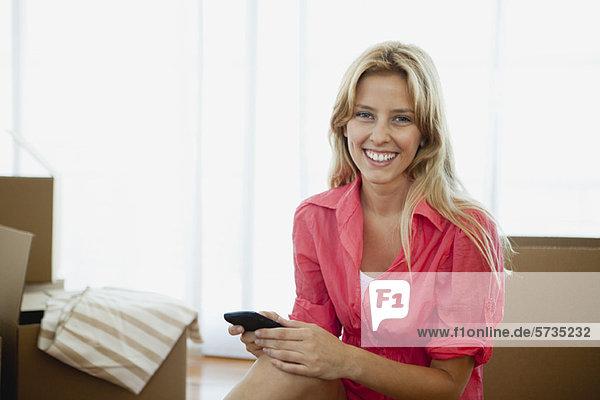 Junge Frau umgeben von Pappkartons im neuen Haus  Portrait