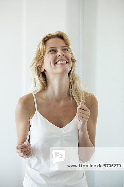 Junge Frau mit Schwangerschaftstest  lachend
