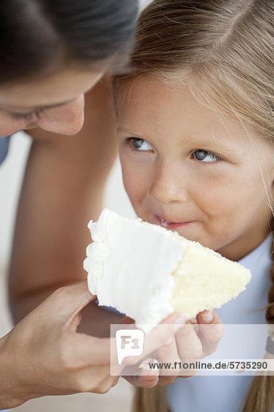 Mutter füttert kleines Mädchen Kuchen
