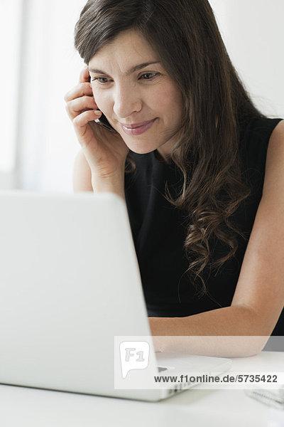 Mittlere erwachsene Frau mit Handy und Laptop