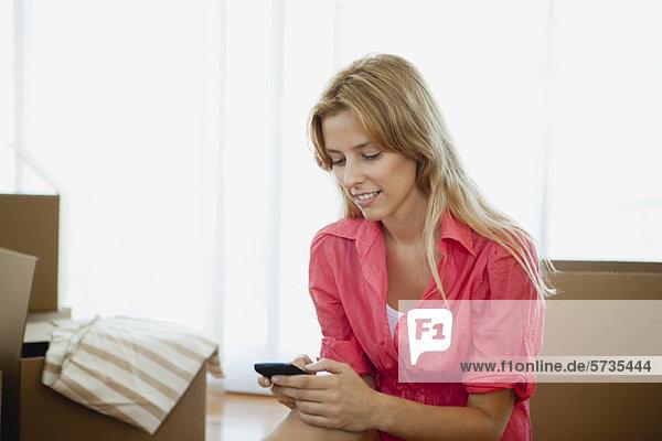 Junge Frau SMS im neuen Haus  umgeben von Pappkartons