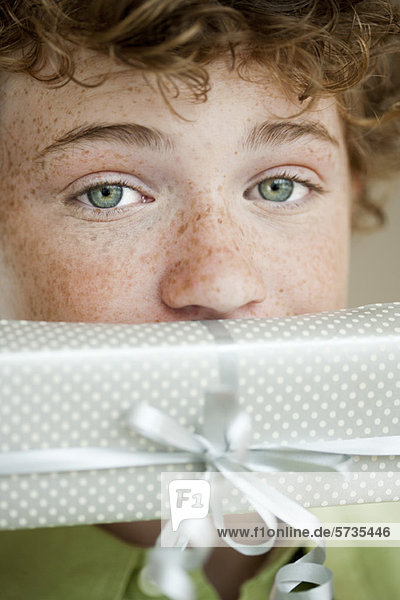 Junge hält Geschenk vor dem Mund  Portrait