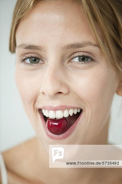 Junge Frau isst Kirsche