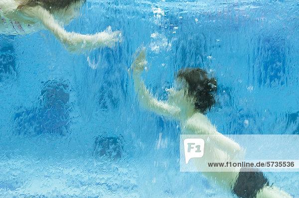Geschwister spielen unter Wasser im Schwimmbad